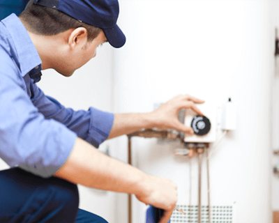 gas fitter adjusting hot water heater controls